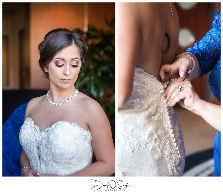 A bride waits patiently as her dress is buttoned.