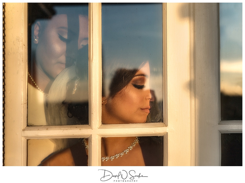 Two brides are pictured on the other side of a window at sunset.