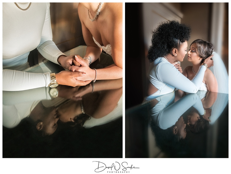 Brides holding hand and kissing above a reflective table.
