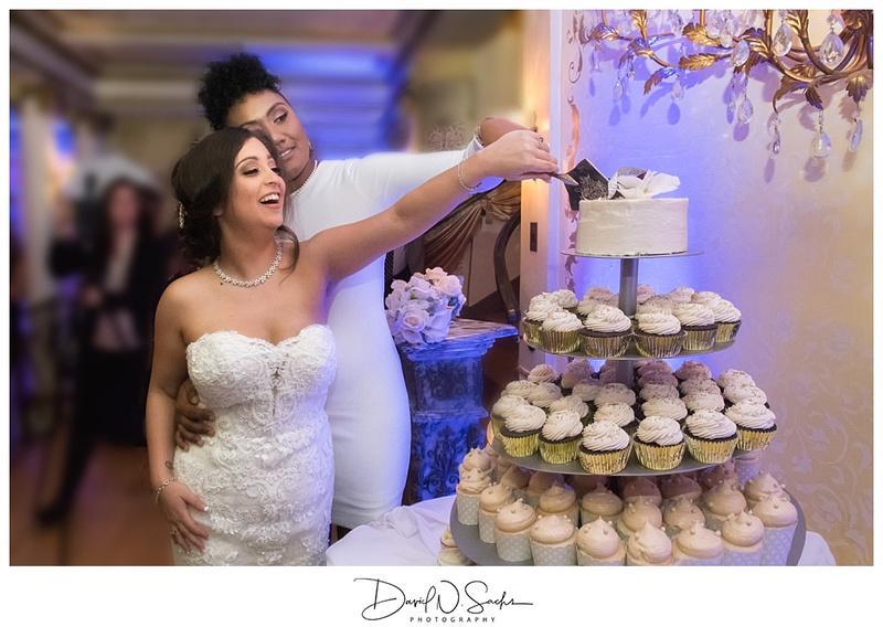 LGBTQ brides reach out and cut their wedding cake.