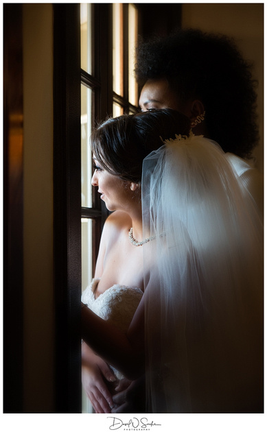 A bride stands behind her wife in a window.