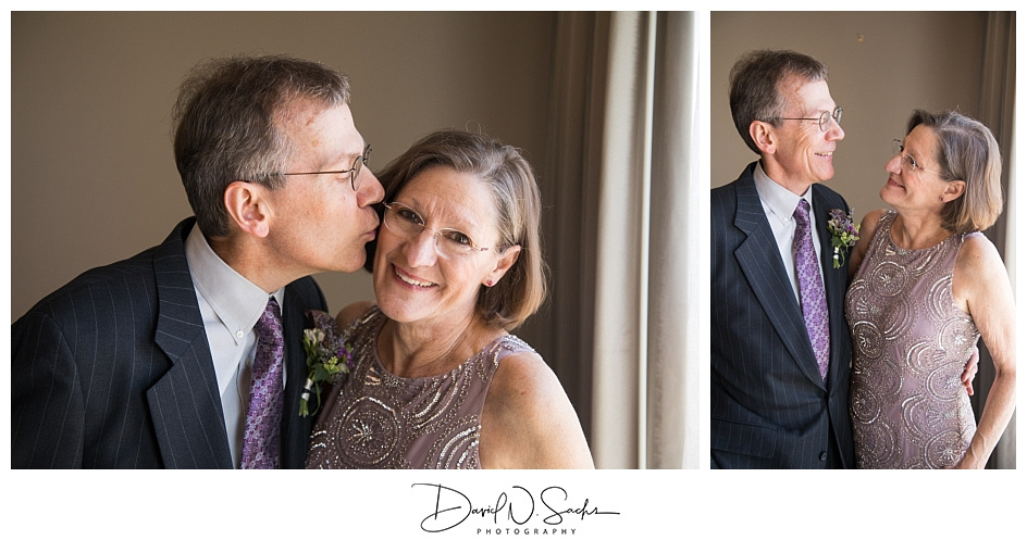 Photos of the brides parents standing in the window of a hotel rom prior to their daughters wedding.