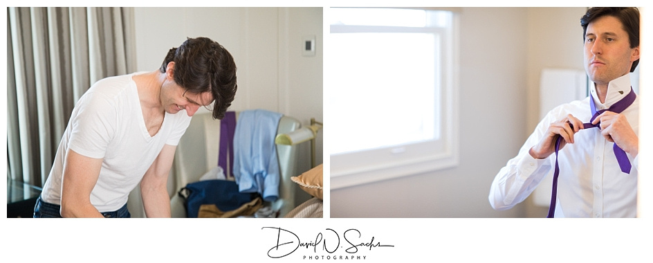 A groom in a white tee smiles and gets ready in his hotel room.