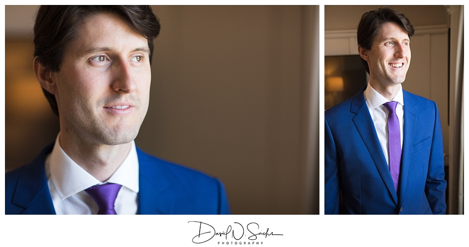 A groom in a blue suit stands in the window of his hotel room at the Hotel Drisco in San Francisco.
