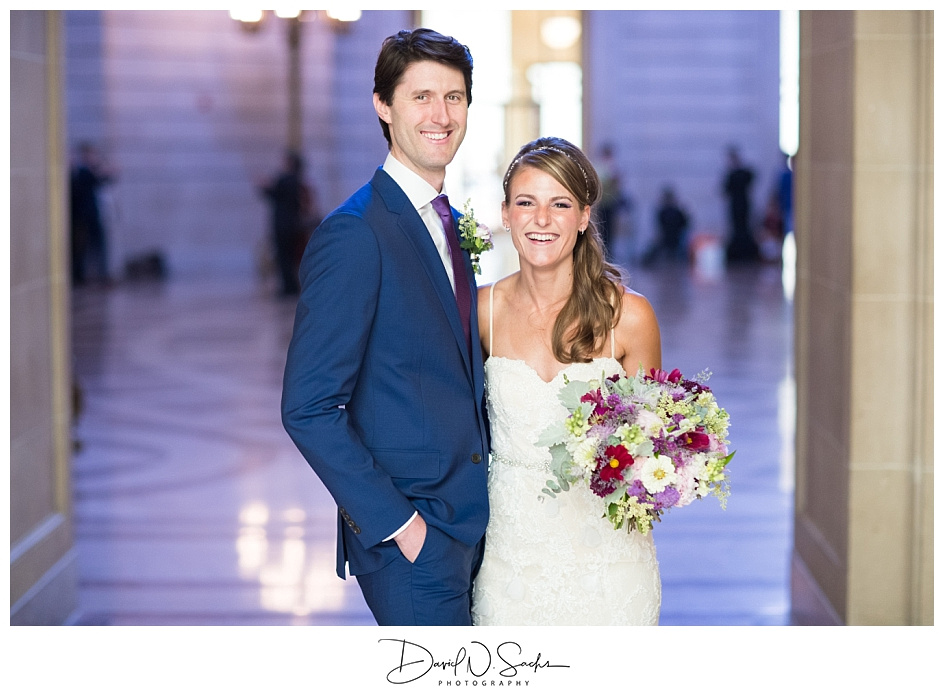 A happy couple smiles at their San Francisco City Hall wedding ceremony.