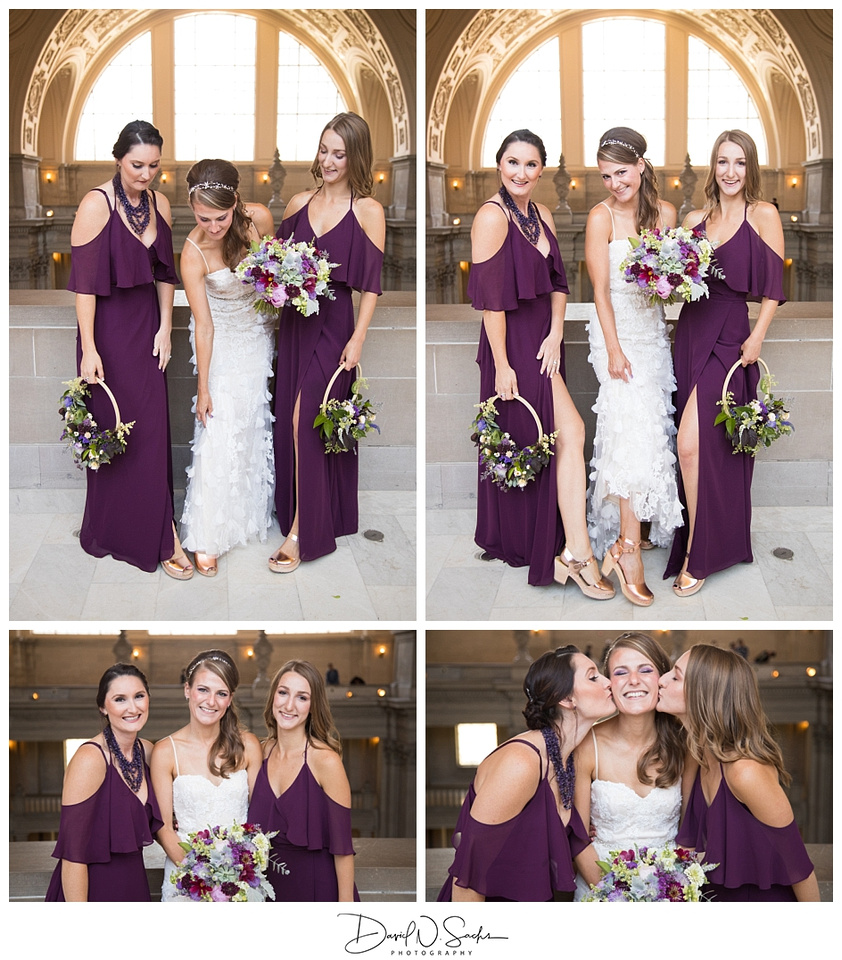 A bride stands with her purple clad bridesmaids holding floral hoops after her San Francisco City Hall wedding ceremony.