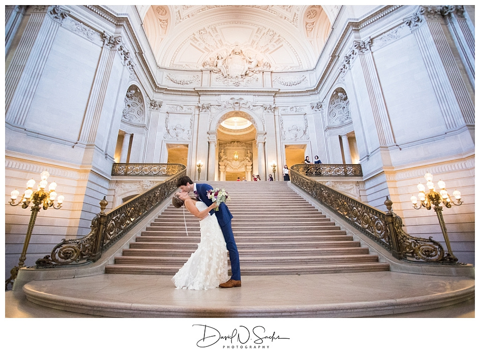A bride and groom kiss and dip after their San Francisco City Hall wedding ceremony.