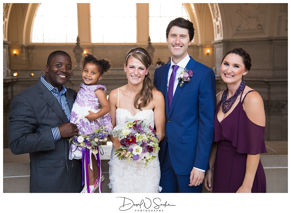A bride and groom smile while standing with the groom's sister at SF City Hall.